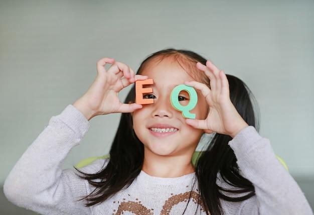 Glückliches kleines asiatisches kindermädchen, das alphabetbuchstaben auf ihrem gesicht hält
