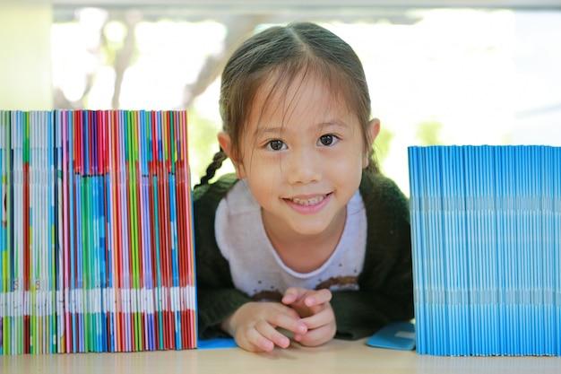 Glückliches kleines asiatisches kindermädchen, das auf bücherregal an der bibliothek liegt