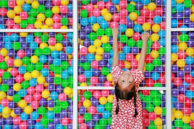 Glückliches kleines asiatisches kindermädchen, das aufstieg spielt und am käfig des bunten spielzeugballs des spielplatzes mit dem schauen der kamera hängt.