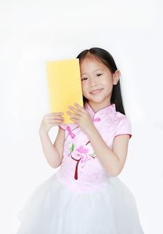 Glückliches kleines asiatisches kindermädchen, das rosa traditionelles cheongsam-kleid lächelnd trägt, während das goldumschlagpaket des chinesischen neuen jahres lokalisiert wird. frohes chinesisches neujahrskonzept.