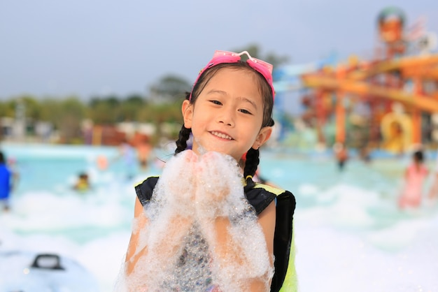 Glückliches kleines asiatisches kindermädchen, das spaß in der schaumpartei am pool habend lächelt