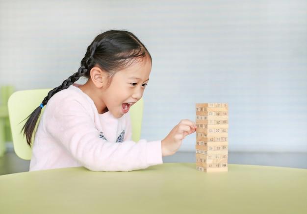Glückliches kleines asiatisches kindermädchen, das turmspiel der hölzernen blöcke für fähigkeit des gehirns und der körperlichen entwicklung in einem klassenzimmer spielt. fokus auf kindergesicht. kid phantasie und lernkonzept.