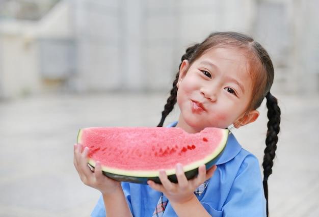 Glückliches kleines asiatisches kindermädchen in der schuluniform genießen, wassermelone draußen zu essen.