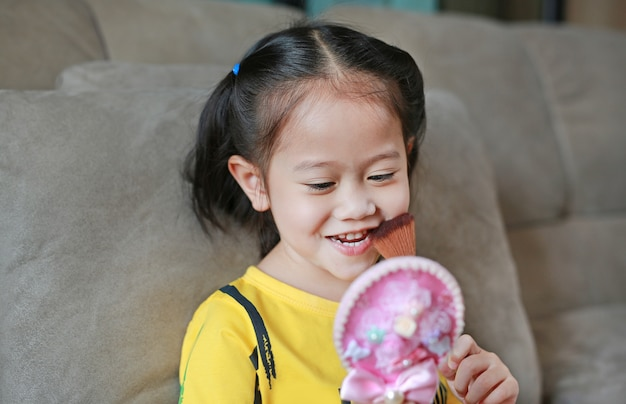 Glückliches kleines asiatisches kindermädchen mit make-up und holdingbürste und spiegel.