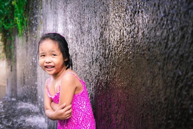 Glückliches kleines asiatisches mädchen, das beim spielen des wassers im überlauf des wehrs kalt sich fühlt