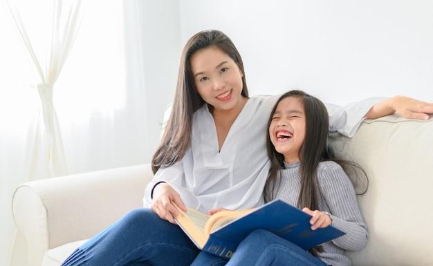 Glückliches kleines asiatisches mädchen, das ein buch im wohnzimmer mit ihrer mutter liest