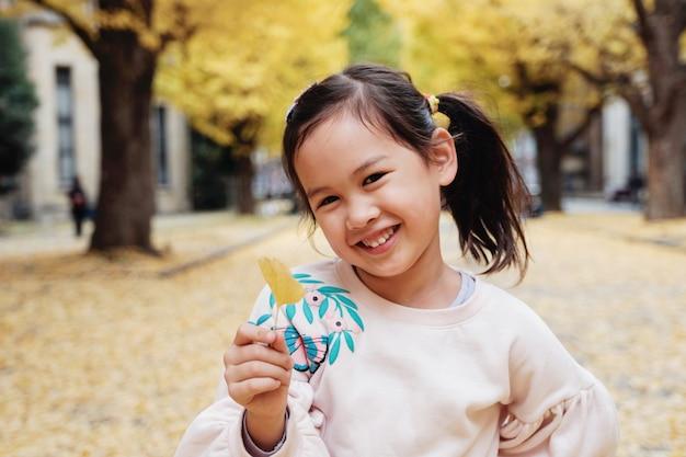 Glückliches kleines asiatisches mädchen, das ein gelbes ginkgoblatt hält und in herbst tokyos japan lächelt