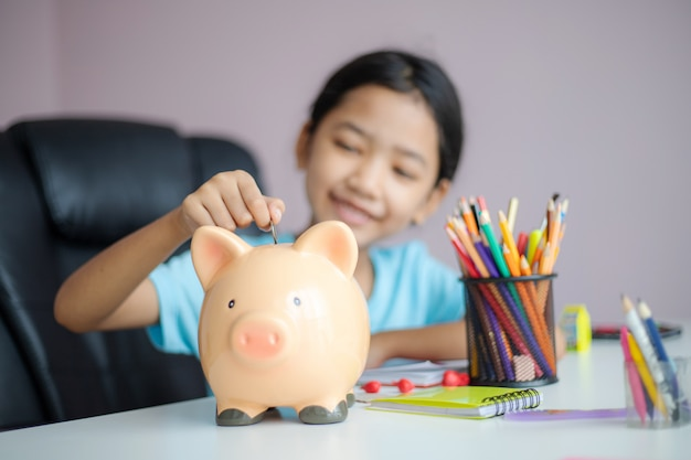 Glückliches kleines asiatisches mädchen, das geldmünze in sparschwein steckt