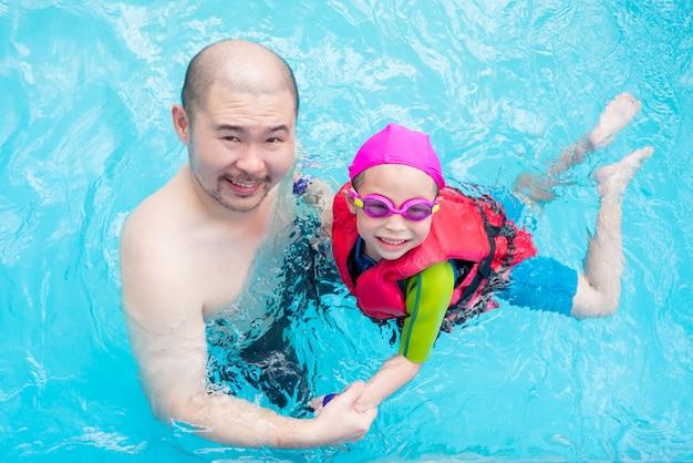 Glückliches kleines asiatisches mädchen, das lernt, mit ihrem vater im swimmingpool zu schwimmen