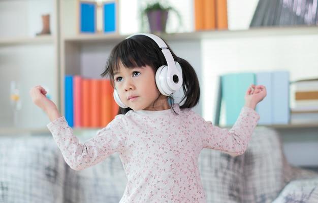 Glückliches kleines asiatisches mädchen, das musik hört