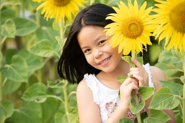 Glückliches kleines asiatisches mädchen, das spaß unter blühenden sonnenblumen unter den sanften sonnenstrahlen hat.
