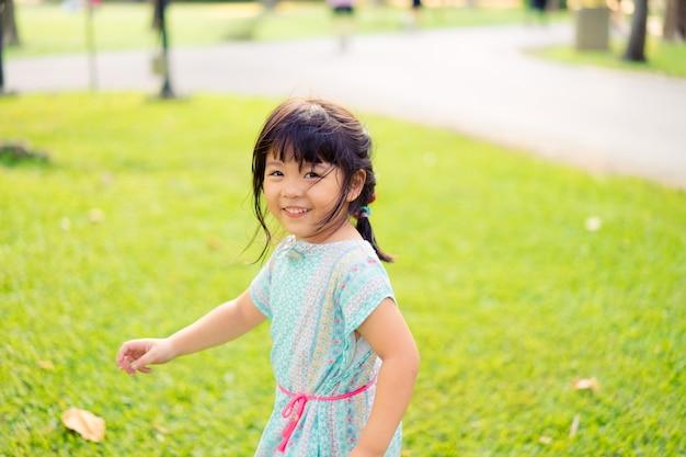 Glückliches kleines asiatisches mädchen, das verstecken auf großem baum mit lustigem moment spielt.