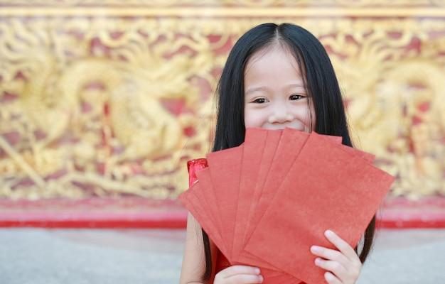 Glückliches kleines asiatisches mädchen, das viele roten umschläge hält. feier des chinesischen neujahrsfests.