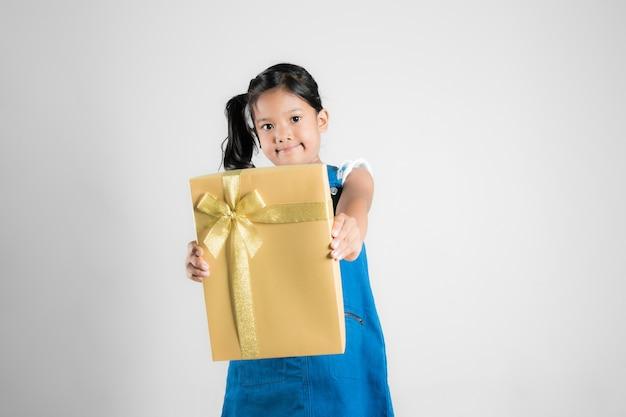 Glückliches kleines asiatisches mädchen gibt goldgeschenkbox