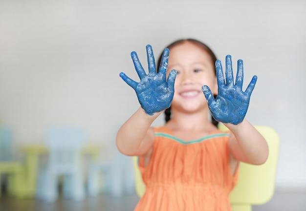 Glückliches kleines asiatisches mädchen mit ihren blauen händen in der farbe im kinderraum