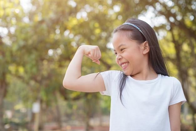 Glückliches kleines asiatisches mädchenkind, das frontzähne mit großem lächeln zeigt. zeigt arme muskeln lächeln stolz, zeigt bizeps .. fitness-konzept.