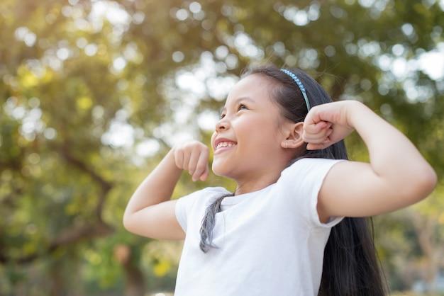 Glückliches kleines asiatisches mädchenkind, das frontzähne mit großem lächeln zeigt. zeigt armmuskeln, die stolz lächeln.