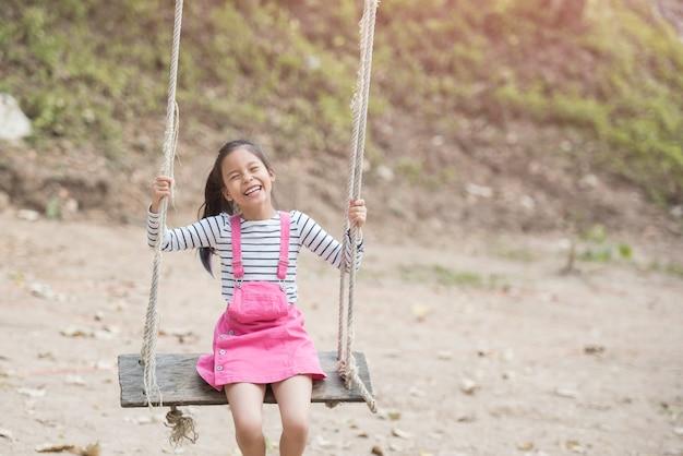 Glückliches kleines asiatisches mädchenkind, das spaß hat, auf dem spielplatz in der sommerzeit mit lächeln und gesundem lachen zu spielen, entzückendes mädchen, das spaß auf einer schaukel im sommer hat.