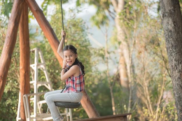 Glückliches kleines asiatisches mädchenkind, das spaß hat, auf dem spielplatz in der sommerzeit mit lächeln zu spielen und gesundes, lustiges lächelndes gesicht entzückendes reizendes weibliches kind zu lachen.