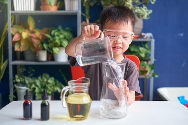 Glückliches kleines asiatisches schulkind, das wissenschaft studiert und diy lava lamp science experiment mit öl, wasser und lebensmittelfarbe macht