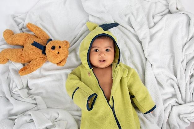 Glückliches kleines baby, das auf weicher decke und lächeln liegt