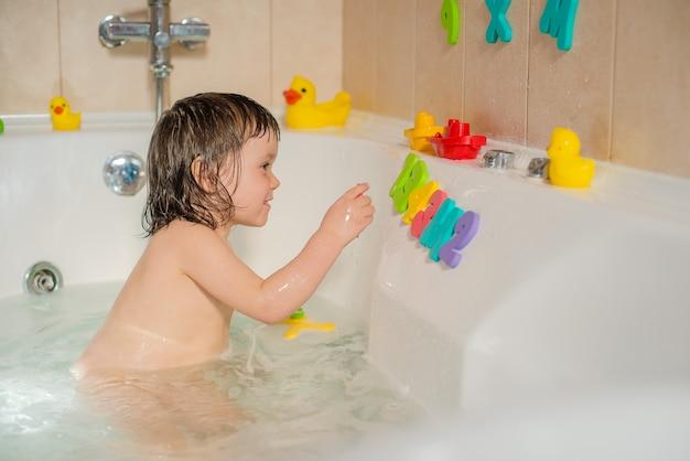 Glückliches kleines baby das badezimmer, das mit schaumblasen und -buchstaben spielt. hygiene und pflege für kleine kinder.