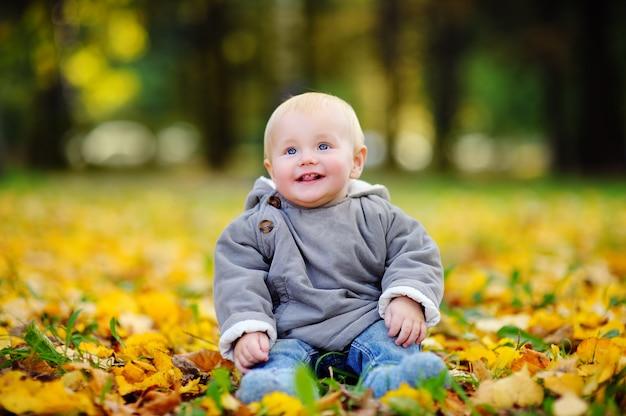 Glückliches kleines baby, das spaß im herbstpark hat