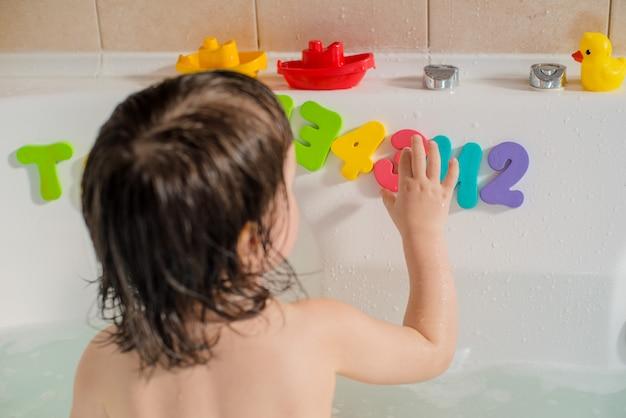 Glückliches kleines baby im badezimmer, das mit schaumblasen und -buchstaben spielt. hygiene und pflege für kleine kinder.