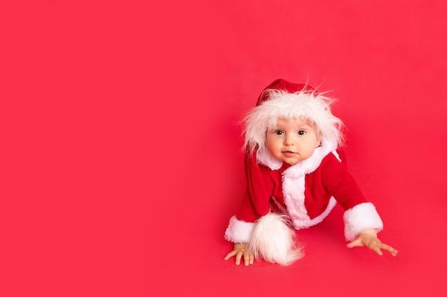 Glückliches kleines baby im weihnachtsmannkostüm, das auf rot lokalisiert krabbelt