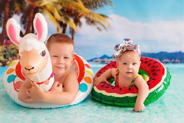 Glückliches kleines baby und mädchen schwimmt im meer in einem rettungsring