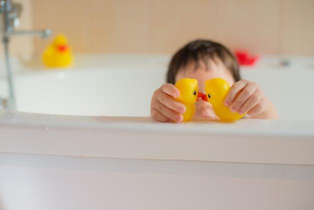 Glückliches kleines babybadezimmer, das mit gelben gummipunkten spielt. hygiene und pflege für kleine kinder.