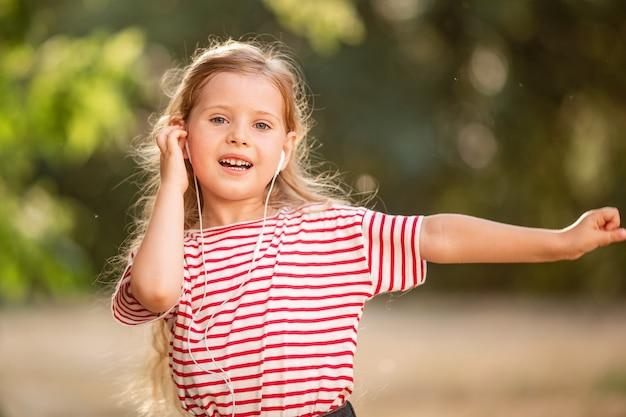 Glückliches kleines blondes mädchen, das musik mit kopfhörern hört, in der natur im park tanzt und singt.