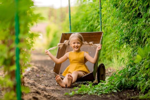 Glückliches kleines blondes mädchen im land in einer gartenschubkarre, die lächelnd sitzt