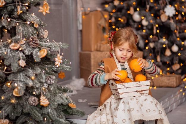 Glückliches kleines blondes mädchen in der skandinavischen kleidung, die mandarinen pflückt und sich auf ein festliches weihnachtsfest vorbereitet