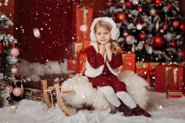 Glückliches kleines blondes mädchen in einer pelzweste und in den kopfhörern, die auf weihnachten und neujahr in der warten