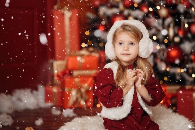 Glückliches kleines blondes mädchen in einer pelzweste und in den kopfhörern, die auf weihnachten warten