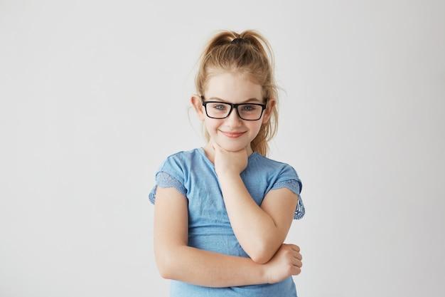 Glückliches kleines blondes mädchen mit blauen augen mit glücklichem und friedlichem ausdruck in der brandneuen schwarzen brille.