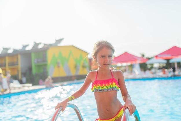 Glückliches kleines hübsches mädchen im farbigen badeanzug verlässt den pool, der an einem sonnigen warmen sommertag am geländer festhält