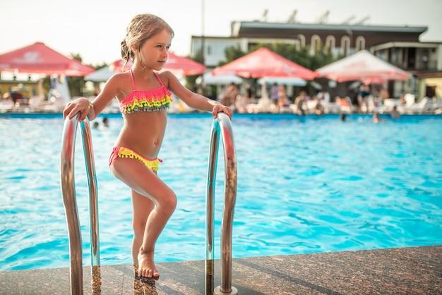 Glückliches kleines hübsches mädchen im farbigen badeanzug