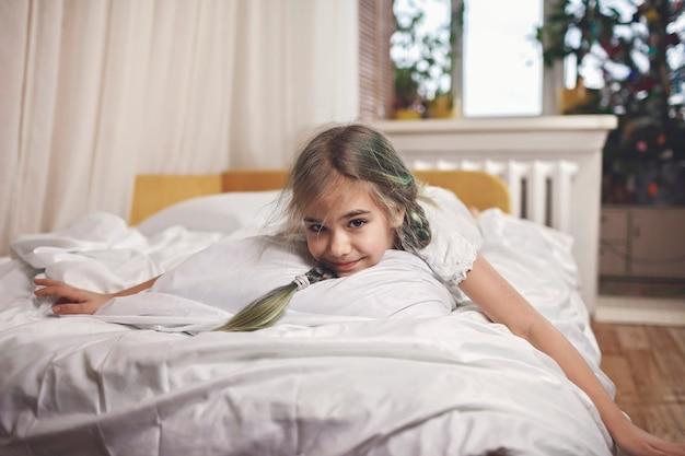 Glückliches kleines im pyjama, das sich morgens im bett entspannt