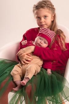 Glückliches kleines jugendlich mädchen, das seine neugeborene kleine schwester hält. familienliebe.