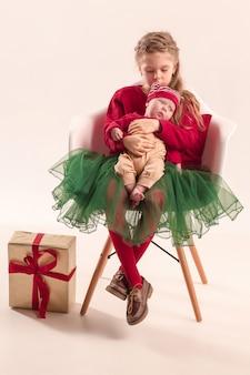 Glückliches kleines jugendlich mädchen, das seine neugeborene kleine schwester im studio hält. familienliebeskonzept. das weihnachts-, feiertagskonzept