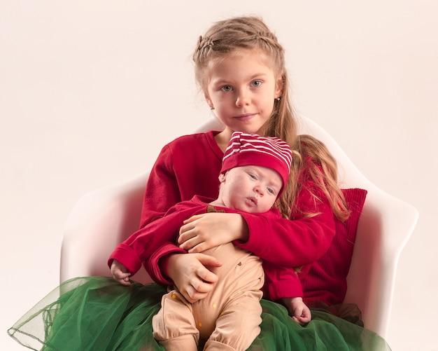 Glückliches kleines jugendlich mädchen, das seine neugeborene kleine schwester im studio hält.
