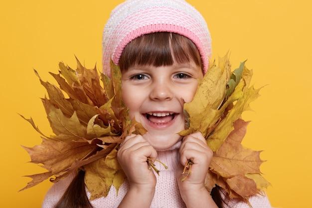 Glückliches kleines kind, baby lacht und spielt mit herbstlaub, schaut vorne mit charmantem lächeln,