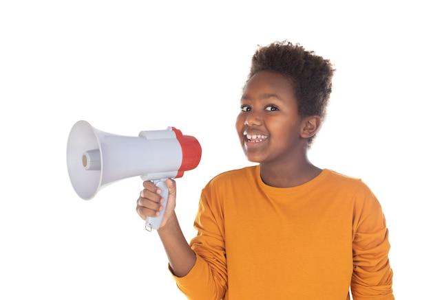 Glückliches kleines kind, das mit einem megaphon spricht, das auf einer weißen wand lokalisiert wird