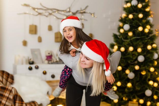 Glückliches kleines kind der mutter und des babys, das im winter für weihnachtsfeiertage spielt