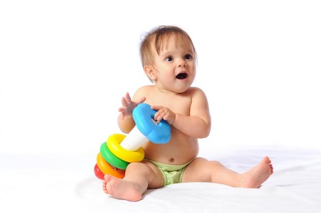 Glückliches kleines kind freut sich über pyramidenspielzeug
