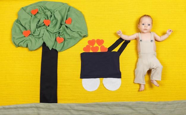 Glückliches kleines kind mit einem wagen voller papierherzen