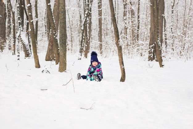 Glückliches kleines kind spielt im schnee, gutes winterwetter.