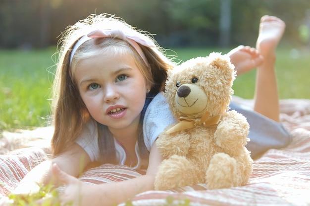 Glückliches kleines kindermädchen, das mit ihrem lieblingsteddybärspielzeug draußen im sommerpark spielt.